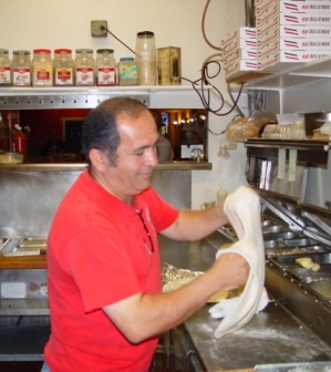 Mario begins to give shape to another great pizza.
