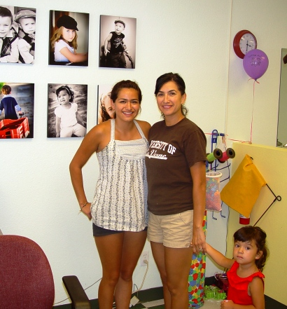Alicia, Maria and Sophia share a moment in front of some of Joanne Distaso's photographs on display at Little Kuts.