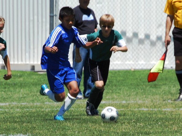 Under 10 boys battle for control of the ball.