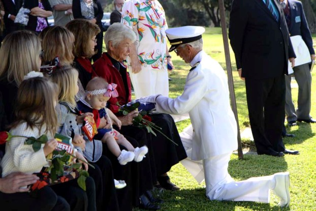 """The folded flag was carried and presented to the widow with the words """"On behalf of the President of the United States, I present you this flag"""".  Margaret Peterson receives the flag from Honor Guard Commander, which was covering her husband's casket just moments before. Photo by Ricardo Tomboc"""
