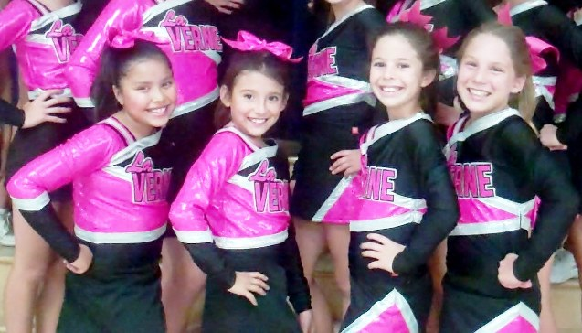 Young La Verne Community Cheer members are all smiles over their new uniforms.