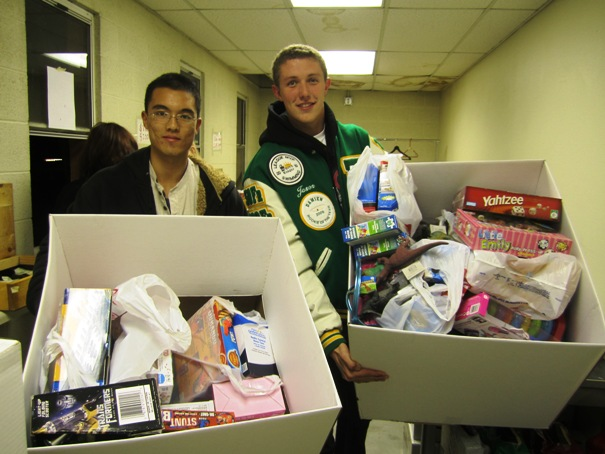 Jacky Yao, left, the founder and president of Damien's student community service outreach club, and Jason Haney, the vice president, hold up two of the 10 large boxes of donated toys at Thursday night's football game. The toys will be given away at Sowing Seeds for Life's fourth annual Christmas in the Park event at Ganesha Park in Pomona on Dec. 3, noon to 4 p.m.