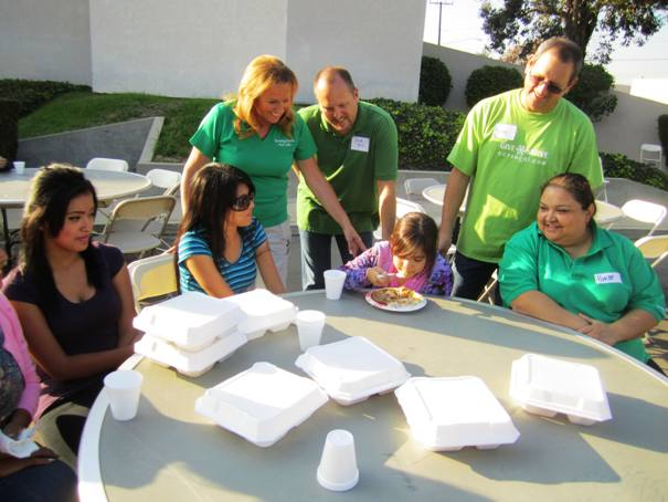 Vicki Brown, pastor David Sill and Michael Collasuonno, a member of the Christ Church of the Valley, and Yvette Carreon of Sowing Seeds for Life look on as 8-year-old Lilandra Pulido enjoys her Thanksgiving meal. With Lilandra is her mother Sandra Pulido. Seated as left is Joyce Ballazares of La Verne.