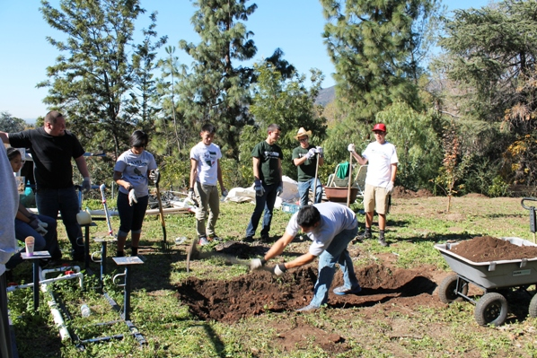 Miguel Martinez, a long jumper on the track team, works on digging hole for the greenhouse's fish tank as other ULV students look on.