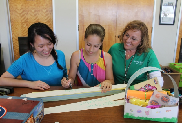 10 -- Volunteer Sylvia Trinh, a junior at the University of La Verne, and Sowing Seeds for Life CEO Vicki Brown, assist 11-year-old volunteer Haley Petersen of Upland in putting finishing touches on Easter baskets.